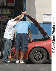 Checking under the hood - couple of men mechanics repairing...