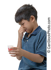 Smelly medicine - Cute boy holding nose while holding some...