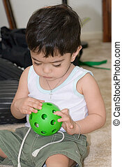Curiosity - young toddler in playing with green ball with...
