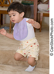 Baby learning to walk - young toddler in purple bib learning...