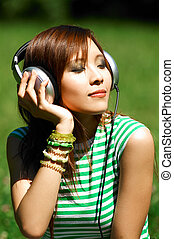 Meadows Girl - Beautiful asian young girl with headphones,...