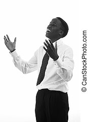 prais b/w - portrait of a young black businessman praising...