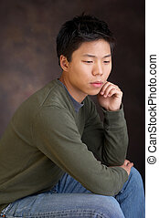 cheerless - portrait of a young asian man thinking