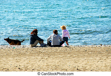 Family relaxing on beach - Family relaxing on a sandy beach