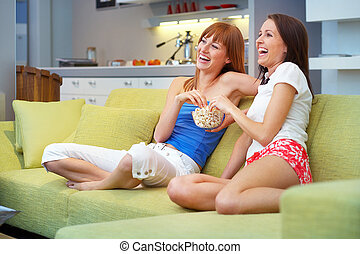 comedy - two girls sitting on the couch watching tv...