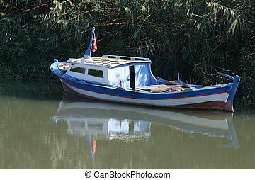 fishing-boat mirrored on water surface