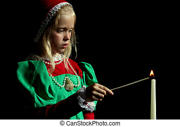 Ancient girl - Little girl lighting candle Black background...
