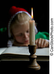 Ancient girl - Little girl reading a book. Black background....