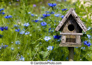 Birdhouse and Flowers - A birdhouse nestles among spring...
