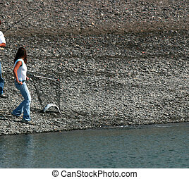 Girl with Net - Lovely young girl netting a salmon during...