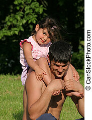 Quality Time - Little girl sitting on the shoulders of her...