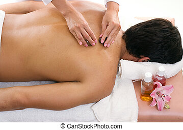 Man receiving thermal stone massage - The therapist applies...