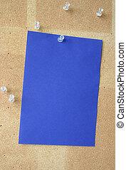 blue paper sheet pinned to corkboard
