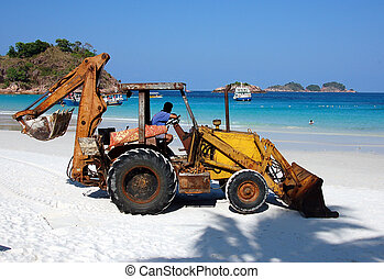 Rusty back hoe on white sand beach - back hoe waiting to...