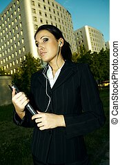 Business Outdoors - Business woman with headphones listen to...