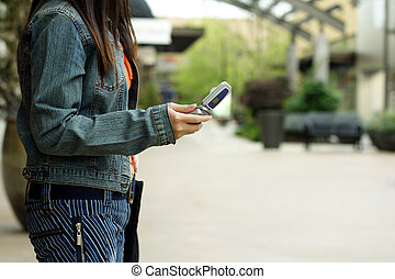 Making a call - A woman with a cellphone in an outdoor...