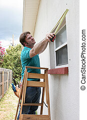 Carpenter Measuring Windows - A carpenter or handyman...