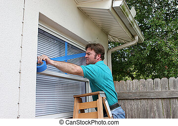 Taping Window - A man taping up his windows to protect from...