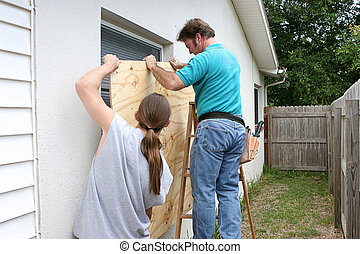 Preparing For Hurricane Together - A father and son working...