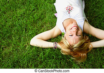 relaxing blond woman - smiling blond woman relaxes on the...