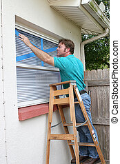 Taping Window Glass - A homeowner or handyman is putting...