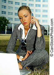 Business Outdoors 2 - Business woman working on grass with...