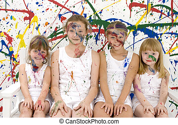 Girl Paint - Four girls covered in paint. Sitting on white...