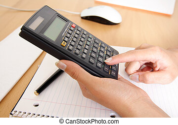 Business finance - A woman uses a calculator