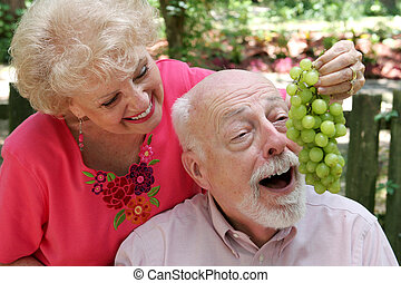 Seniors Having Fun - A senior couple joking around She is...