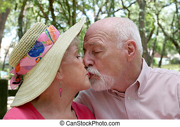 Keep Romance Alive - An attractive senior couple kissing...