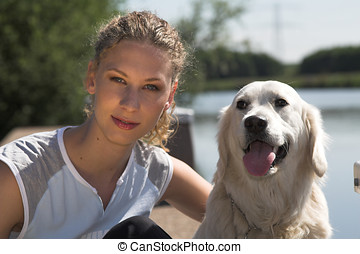 Relaxing with the dog - Beautiful curly blond woman sitting...