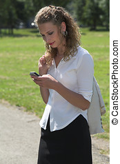 Businesswoman in the park sending a text message -...