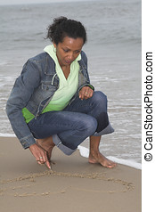 Drawing a heart in the sand - Beautiful black woman drawing...