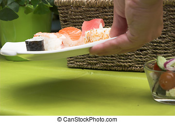 Putting down the sushi plate - Hand reaching to the table to...