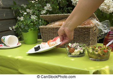 Adding a plate of sushi to the picknick table - Hand adding...