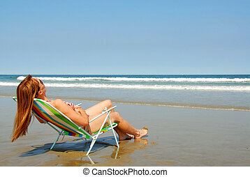 Woman relaxing on beach - Young woman relaxing in a beach...