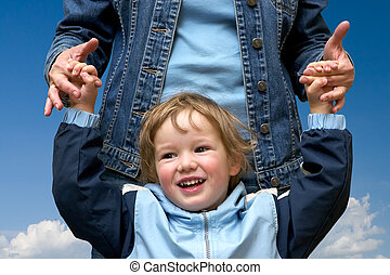 Happy child with mum cheerfully play on a spring meadow