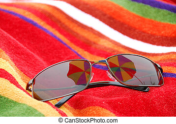 Beach sunglasses - Sunglasses on beach towel relfecting...