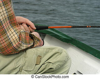 Patient Fisherman - A fisherman relaxing on his small boat