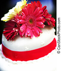 wedding cake with flowers on top of it and red ribbons...