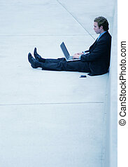 Business man with laptop - Business man in black suit...