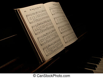 music book - hymnal open on old piano