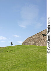 Woman Walking on Grass Bank Stirling Castle in Scotland UK