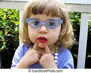 playing dress up - Little girl with glasses, lipstick,...
