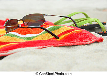 Beach items on sand - Beach towel, sunglasses and flipflops...