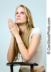 Praying blonde girl - Praying blond girl kneeling on a...