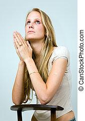 Praying blonde girl. - Praying blond girl kneeling on a...