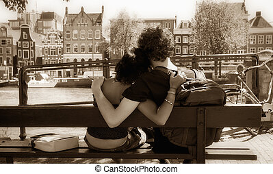 couple hugging - sweet young couple sitting on a bench and...