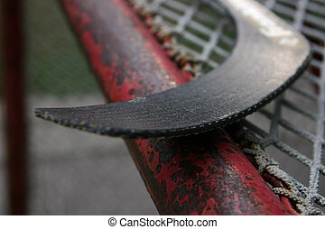 Hockey II - A hockey stick on top of a hockey net