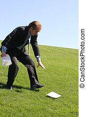 Falling apart - Business man walking down grassy hill trying...